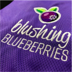 Blushing Blueberries Embroidered with blueberry above with purple background. Service used was Embroidery in Coffs Harbour.